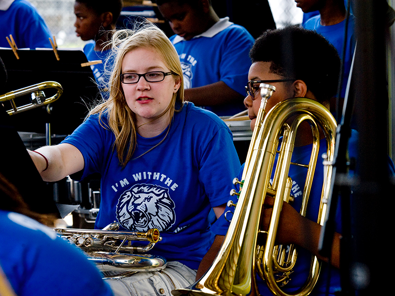 Tulane Service Learning student helping young band member